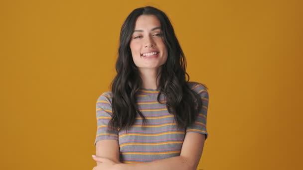Usmívající se mladá žena posílá vzdušný polibek divákovi stojícímu izolovaně nad žlutým pozadím