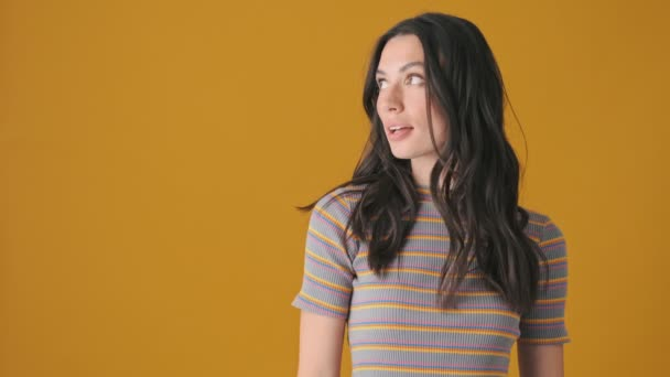 A shocked emotional young woman is pointing to the free space standing isolated over yellow background