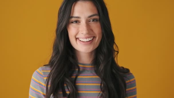 A happy young woman is smiling to the camera isolated over yellow background