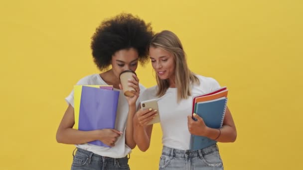 Beautiful students women are using a smartphone standing isolated over a yellow background
