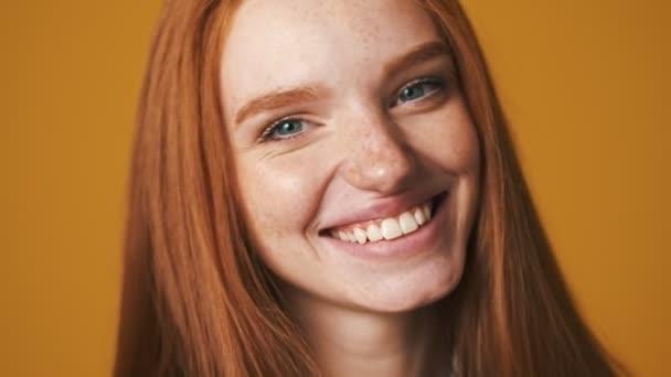 A közeli kép egy boldog fiatal nő mosolyog, miközben pózol a kamera elszigetelt barna háttér