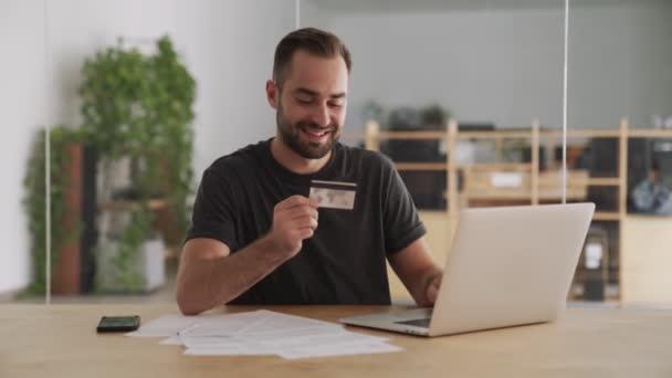 Junger positiver glücklicher Mann drinnen im Büro mit Laptop und Kreditkarte