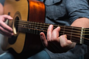 acoustic guitar in the hands of the guy on the whole frame