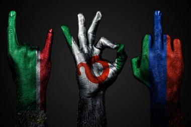 a set of three hands with a painted flag of Ingushetia, Dagestan and Chechnya show middle finger, goat and Okay, a sign of aggression, protest and approval on a dark background.