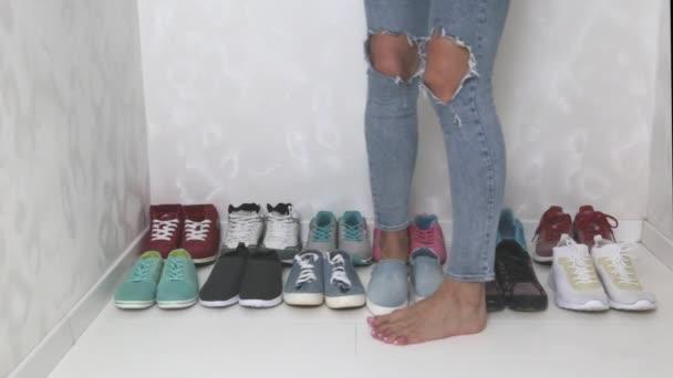 Eine sportlichere Mädchen in Jeans wählt die Turnschuhe Schulung machen. Mehrere Paare von Sportschuhen und Beine.
