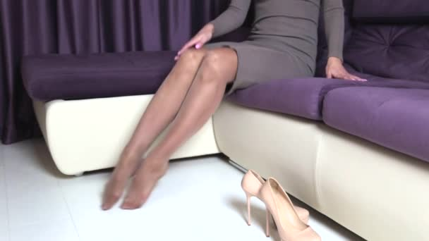 Unavená žena sundá její boty s vysokými podpatky a masáže nohou