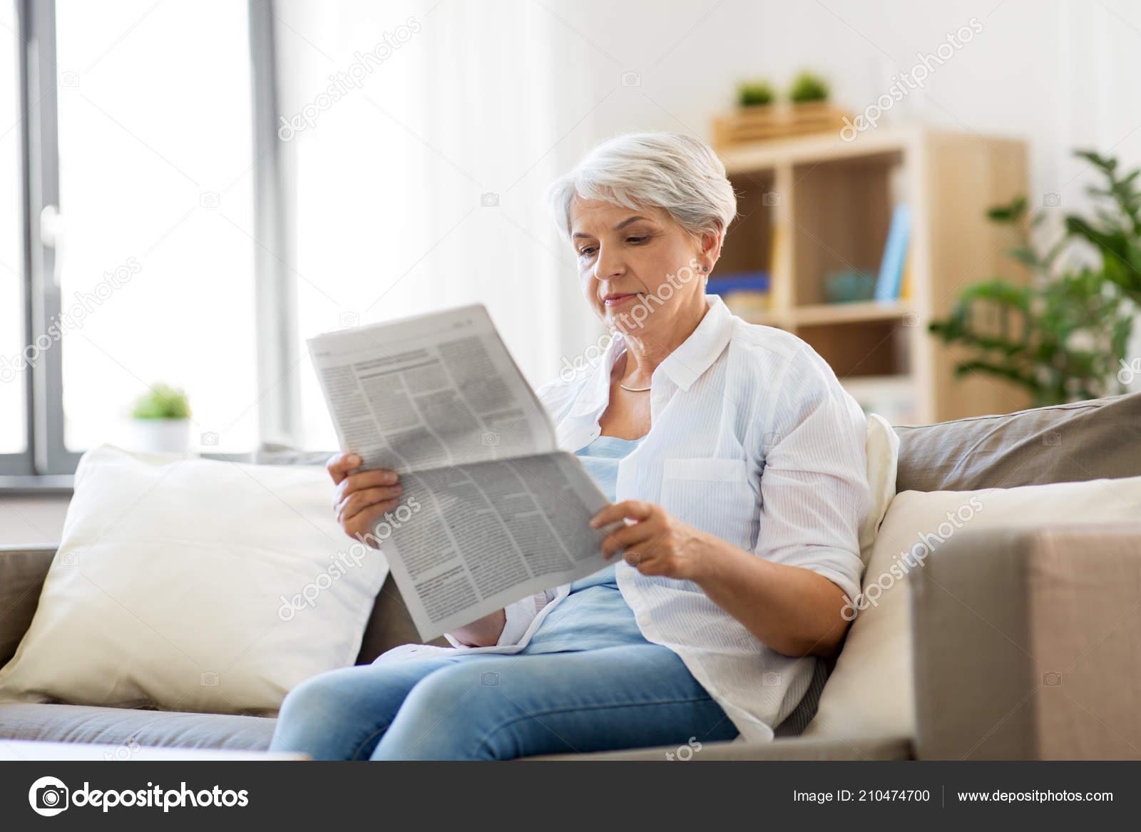 senior woman reading newspaper at home — stock photo