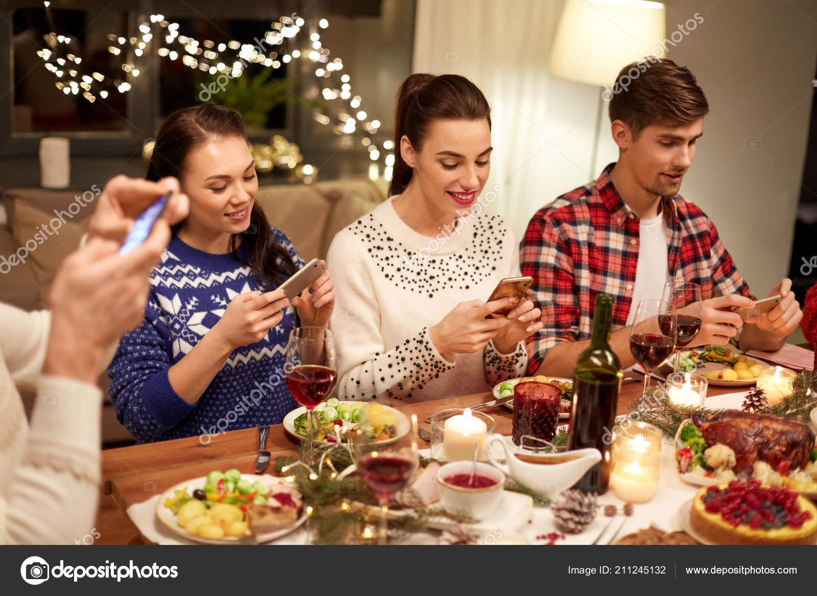 Fotos Cena Navidad Frinsa.Friends With Smartphones Having Christmas Dinner Stock