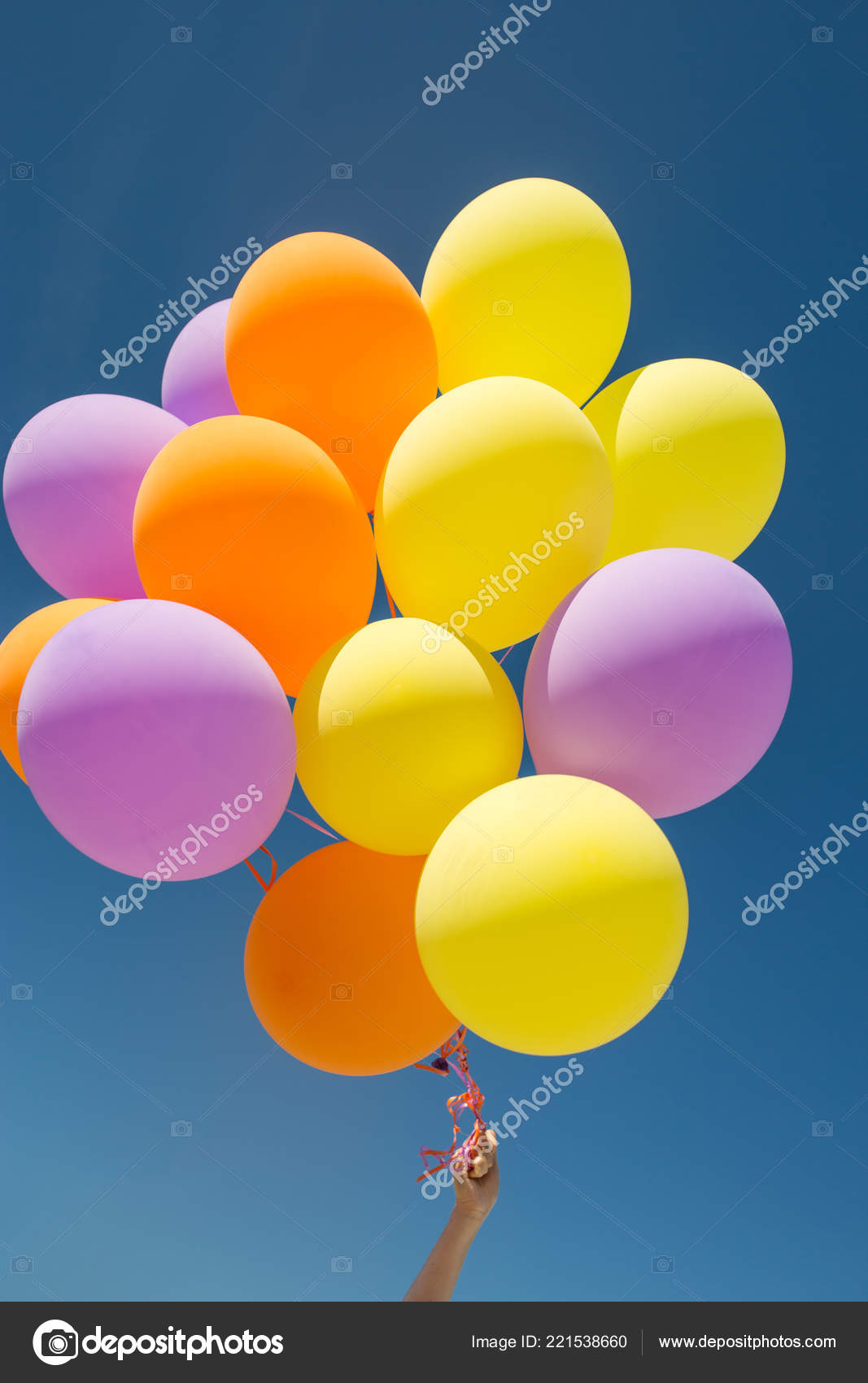 close up of colorful helium balloons in blue sky stock photo