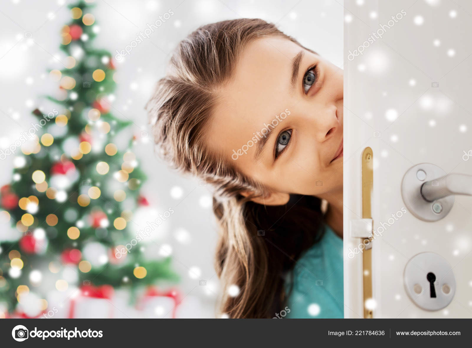 Christmas and people concept - happy smiling beautiful girl looking out open door at home — Photo by Syda_Productions
