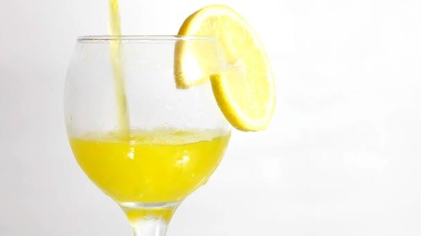 Detailní záběry citronu nápoje nalil do sklenice na bílé