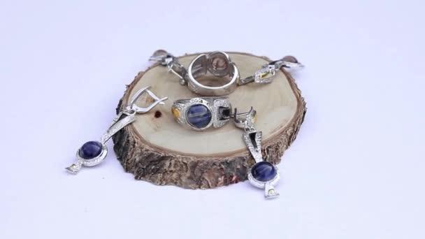 stříbrné náušnice a prsteny na kusu dřeva izolovaných na bílém pozadí, zblízka