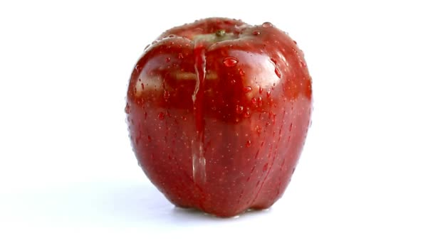 close-up footage of red apple on white surface covering with water drops
