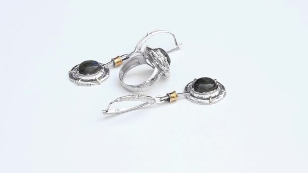 stříbrné náušnice a prsten izolovaných na bílém pozadí, zblízka