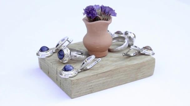 presentazione di orecchini in argento e anelli sul pezzo di legno isolato su priorità bassa bianca, primi piani