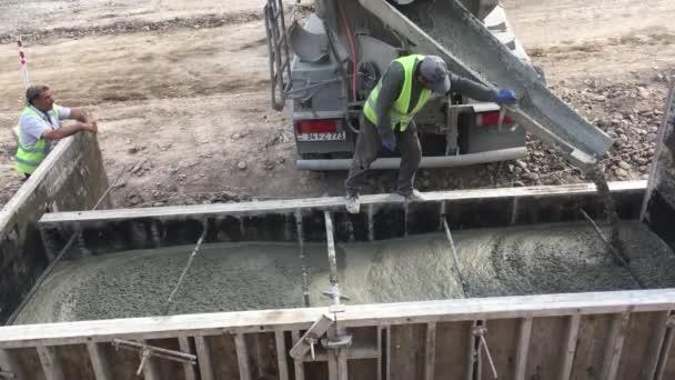 Filmaufnahmen von Bauarbeitern, die auf der Baustelle eines modernen Gebäudes mit Beton arbeiten