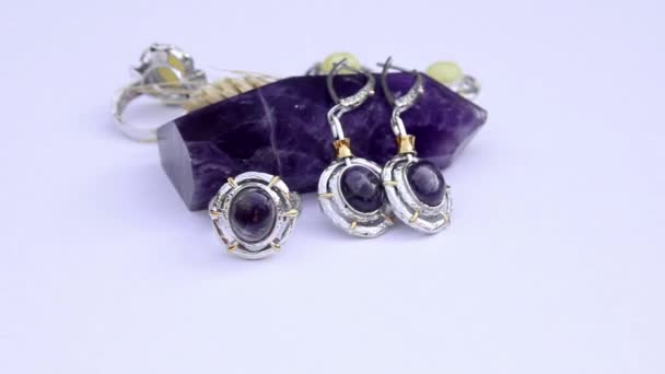 presentation of silver earrings and rings with colorful gemstone isolated on white background, close up