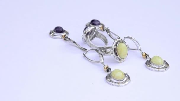 stříbrné náušnice a prsteny izolovaných na bílém pozadí, zblízka