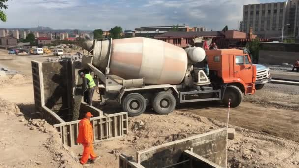 footage of builders working with concrete on construction site of modern building