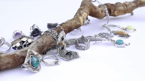 presentazione di orecchini in argento e anelli sul pezzo di driftwood isolato su sfondo bianco, primi piani