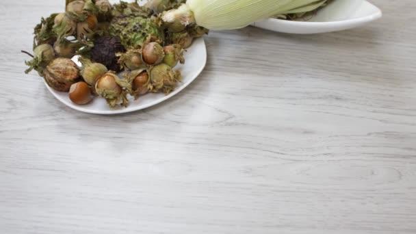 Zblízka pohled na zralý kukuřičný klacek a ořechy na kuchyňském stole