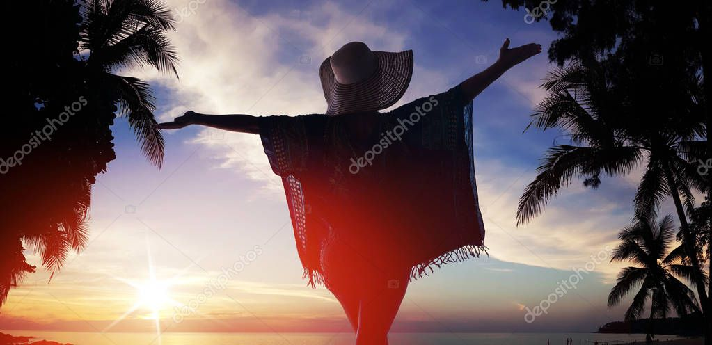 Relaxed lady looking at the sunset on tropical beach