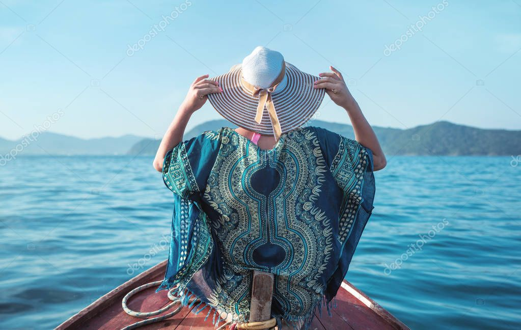 Young, relaxed woman on a small asian boat - tropical panorama