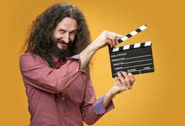 Funny, skinny nerd holding a clapperboard stock vector