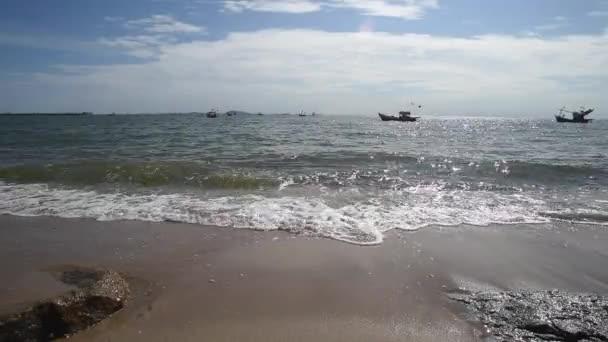 Sea surf with fishing boat mooring at sea