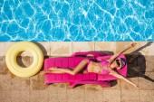 Nagy szög lövés, boldog fiatal nő a nyugágyban a medence mellett pihentető rózsaszín bikini