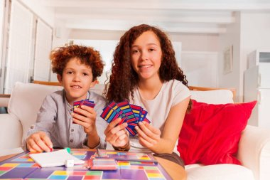 Portrait of age-diverse kids playing card games in the living room and looking at camera