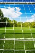 Fotbalová síť a fotbalový stadion na pozadí na čistou prázdnou hřišti pro děti prostřednictvím brány