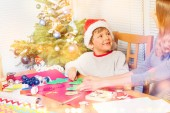 Photo Happy preschool boy in Santas hat attaches Christmas stickers and makes holiday decorations with mom