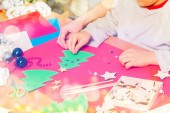 Photo Close-up of kids hands makes holiday decorations, attaches colorful stickers on paper Christmas tree