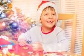 Süße junge eigenen Urlaub Ornamente, sitzt neben dem Weihnachtsbaum zu Hause