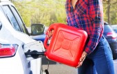Fotografie Detail of woman with red plastic can filling car tank at the parking lot outside