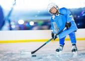 Portrét happy Boy, malý hokejista, stojící na kluziště a předávání PUK