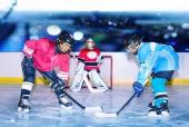 Boční pohled portrét dvou dospívajících chlapců, hokejová pravá křídla, jde o PUK u net na kluzišti