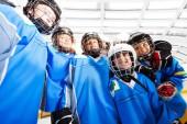 Fotografie Nízký úhel pohled s úsměvem chlapce, lední hokej, stojící dohromady a objímání po úspěšné hry