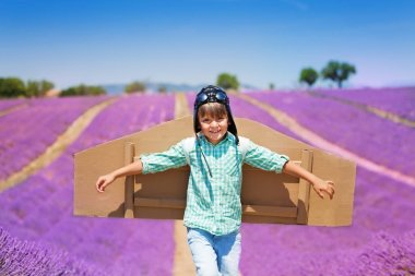 Happy little boy wearing aviator hat and cardboard wings, running through the lavender field in summer