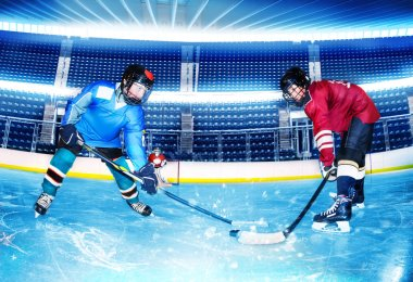 Portrait of two teenage boys, professional hockey players, challenging for the puck at stadium