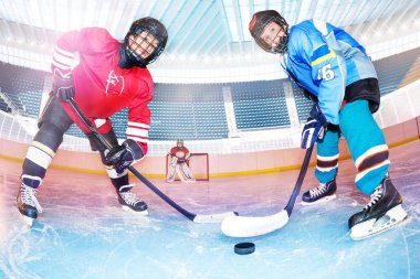 Low angle portrait of teenage boys, hockey players, challenging for the puck on ice rink