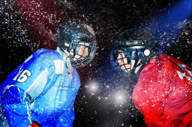 Close up portrait of two teenage boys, ice hockey players, standing face-to-face, floodlighted over dark background