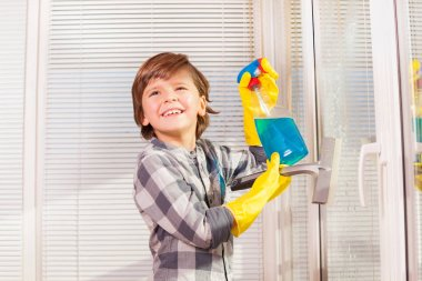 Portrait of happy little boy in protective gloves spraying detergent and cleaning windows indoors