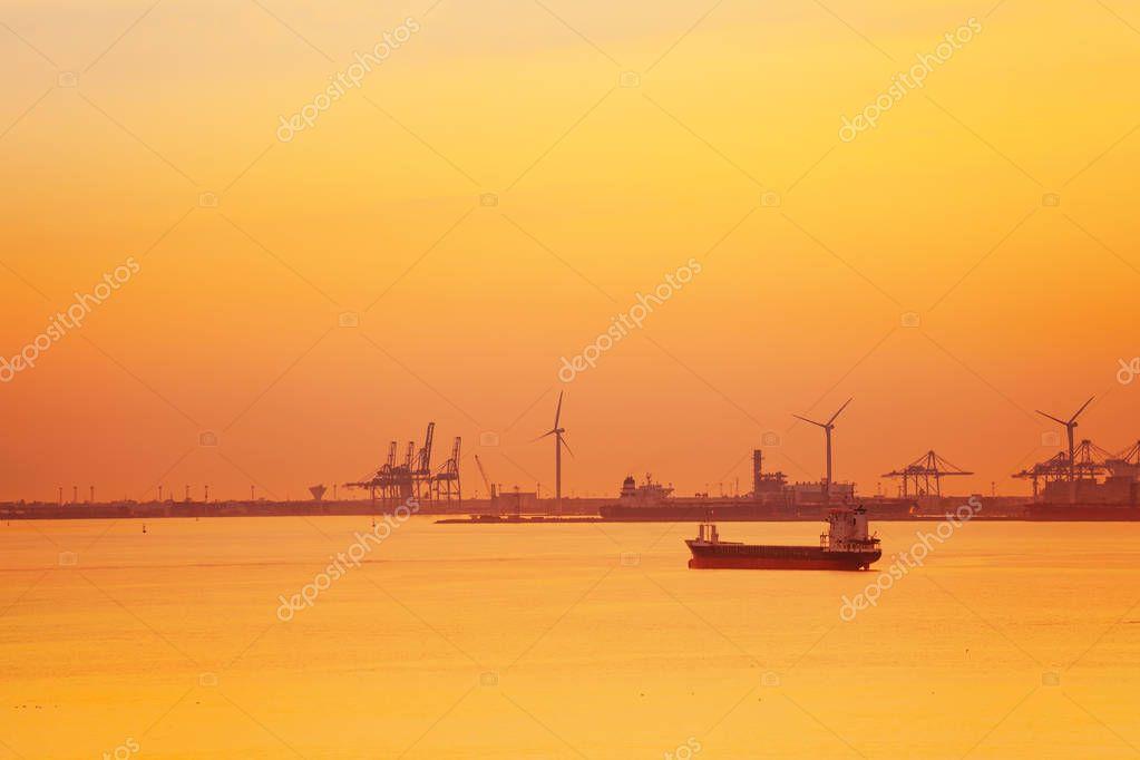 Port de Bouc petrochemical platform with wind turbines, portal cranes and tanker at twilight
