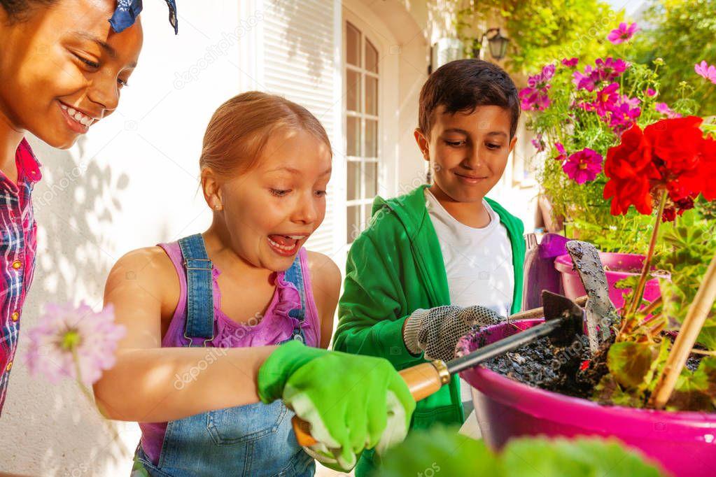 Portrait of three happy friends, preteen girls and boy, planting red geranium in flowerpot outdoors