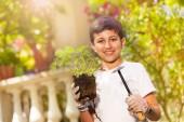 Photo Close-up portrait of preteen boy wearing gardening gloves, holding strawberry plants and garden trowel