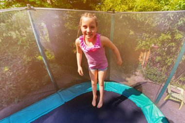 High angle portrait of happy girl bouncing up on the trampoline outdoors
