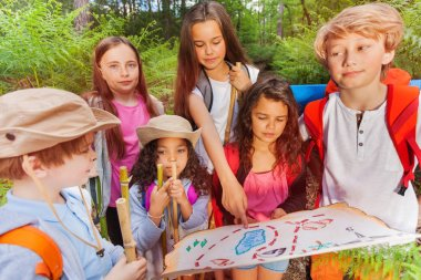 Group of kids in forest examine and point with finger on map during treasure hunting hike activity in summer camp