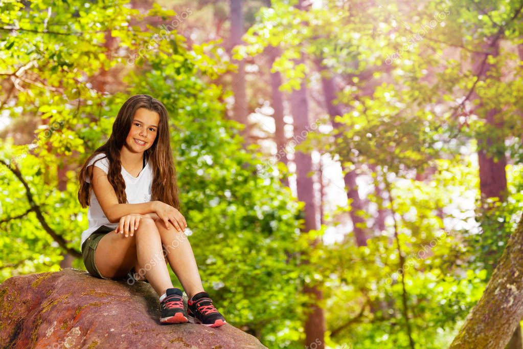 Little girl sit on stone in the forest in casual clothing full height portrait